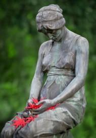 Traurig nach unten blickende Frau aus Stein